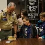 The boys weighing in their pinewood derby cars
