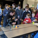 Alex at a cubing competition with his fans lined up for autographs