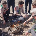 Boys competing in firestarting-trying to burn the rope in half
